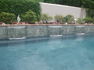 Waterfalls pouring out of raised wall on pool.