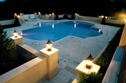 Pool with travertine decking, four laminar deck jets.