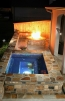 An all tiled spa with a stone fire pit built near by.